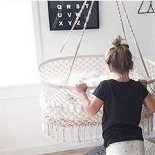 baby ligt in witte hangwieg en een klein meisje staat naast de wieg en leunt op de zijkant, waardoor de wieg een beetje scheef hangt