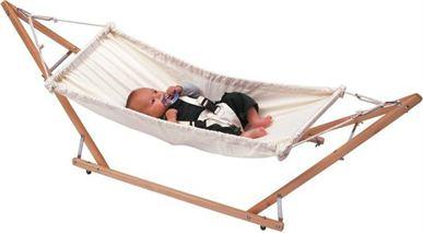 Een pasgeboren baby ligt op de rug in een klein wit hangmatje