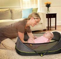 een mamma legt haar kleine baby in de brica opvouwbare reiswieg op de grond.