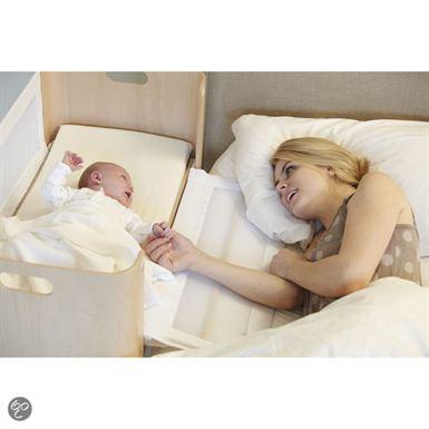bednest wieg met een baby er in. staat vast aan het bed van mamma terwijl mamma vanuit het bed naar de baby kijkt