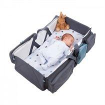 Een pasgeboren baby slaapt in een donkergrijze reiswieg met een klein bruin knuffelkonijntje in de linker bovenhoek