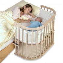 een klein wiegje dat vast staat aan het bed van de mamma. Het hekje aan de ene kant is weg, zodat de mamma bij haar baby kan.