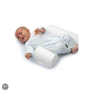 een baby die slaapt in een rond zijligkussen. een cilinder voor de buik en een langere cilinder in de rug