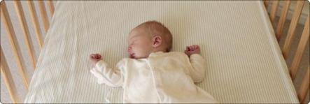 een pasgeboren baby die slaapt in een wiegje zonder dekentje met armpjes omhoog