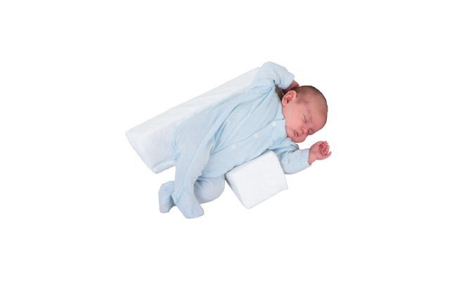een baby slaapt op een driehoekig zijligkussen. een grote prisma in de rug en een kleine prisma voor de buik